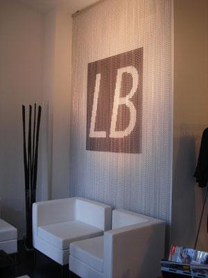 Sala de espera, detalle de cortina metalica con logotipo de la empresa.