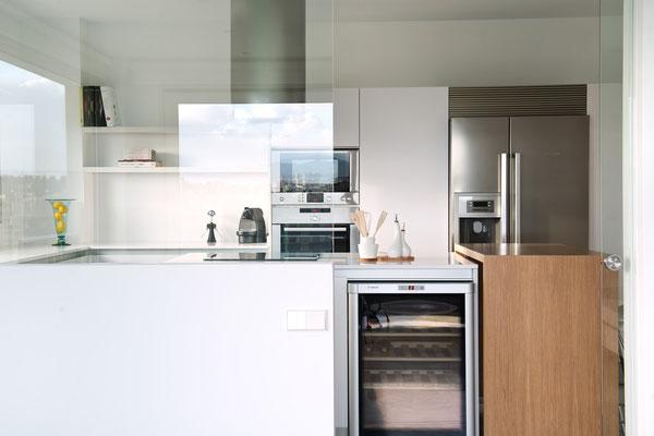 Cocina blanca, con electrodomésticos en acero.