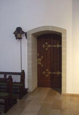 Eingang zur Sakristei mit der Glocke, einem Geschenk der Partnergemeinde Velemes