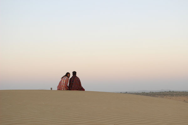 two people sitting on a dune