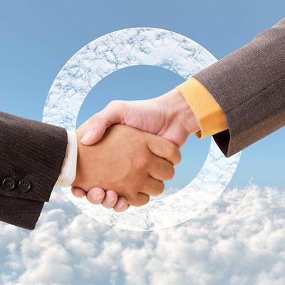スーツ姿の人物が固く握手を交わしている画像
