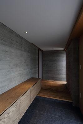玄関 杉板仮枠RC壁と、オーク材の構成