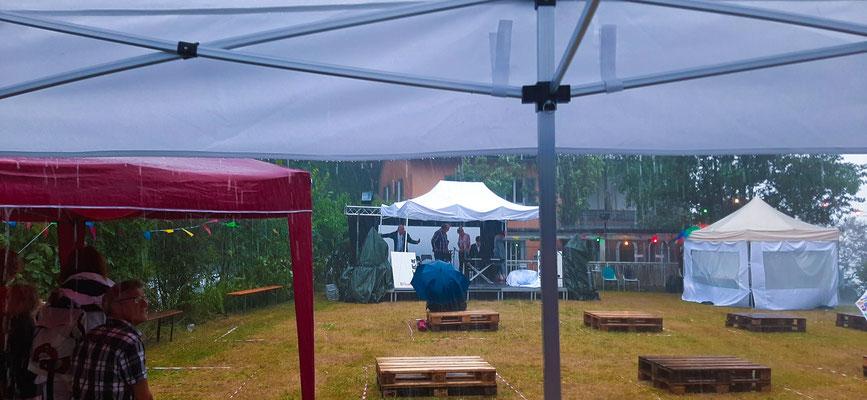 09: Auch der zwischenzeitliche strömende Regen hält die Besucher:innen  nicht davon ab zu bleiben (Foto von Michael Maier)