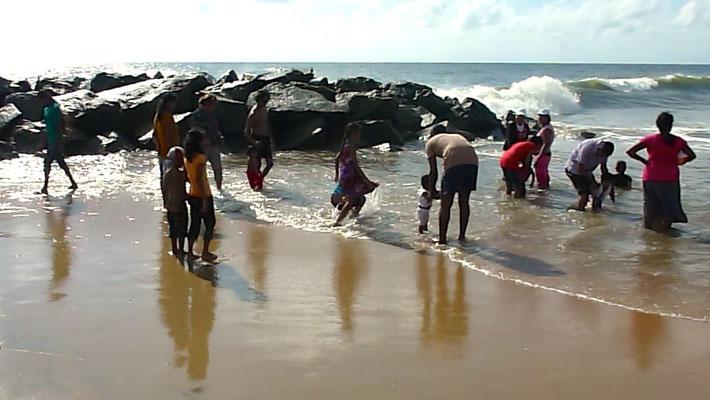 Bild: Negombo Beach Strand - Menschen stehen im Wasser, um sich abzukühlen