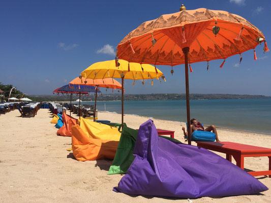 Bild: Farbenfrohe Sonnenschirme und Liegen am Strand von Jimbaran