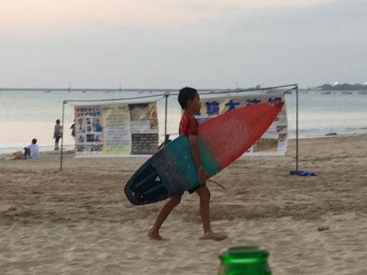 Bild: Kleiner Surfer mit seinem Surfbrett auf dem Weg zum Wasser