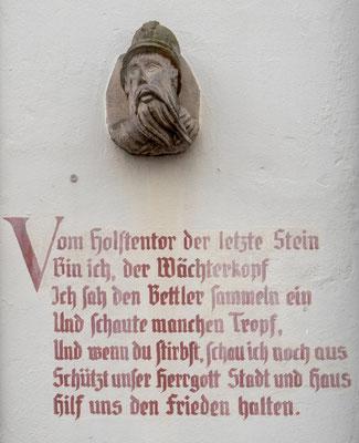 Bild: Der Wächterkopf im Altholsteiner Hof mit Text