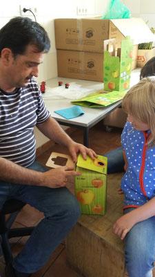 Lina lässt sich erklären, wie die Kartons verpackt werden.