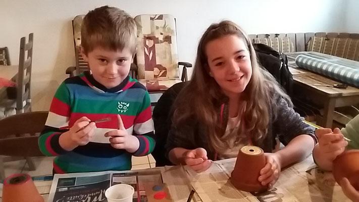 Timo und Paulina bemalen ihren Tontopf.