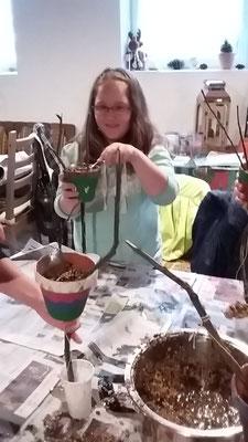 Joy befüllt ihren Tontopf.