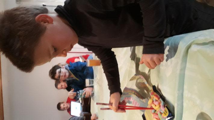 Simon versucht mit Stäbchen Würmer zu essen.
