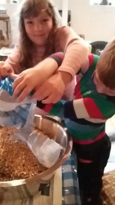 Rosalie und Timo schütten die Körner in eine Schüssel.