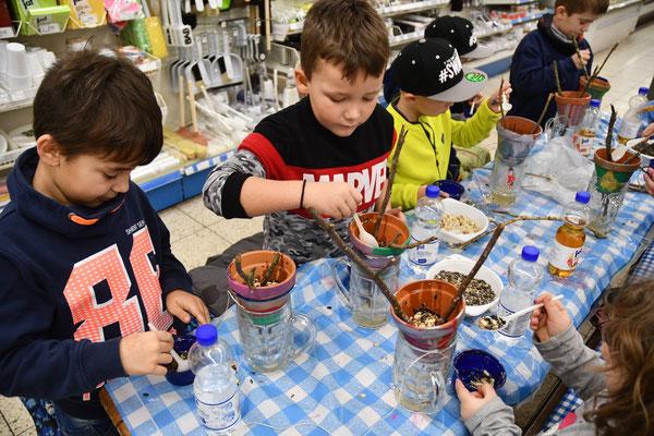 Die Kinder befüllen die Töpfe mit der Futter-Fett-Mischung,