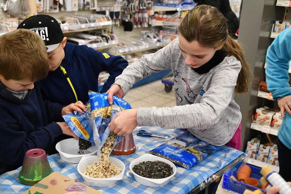 Die Kinder verteilen das Futter in Schüsseln.