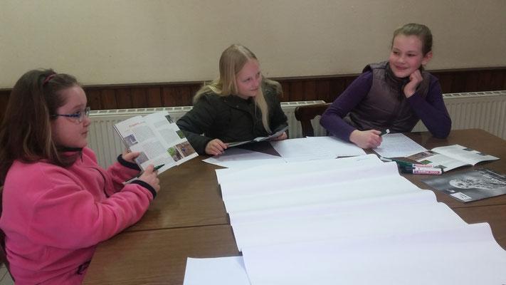 Joy, Lisa und Lana suchen Infos aus den Broschüren