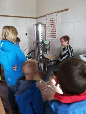 Die Kinder schauen zu, wie der Saft abgefüllt wird.
