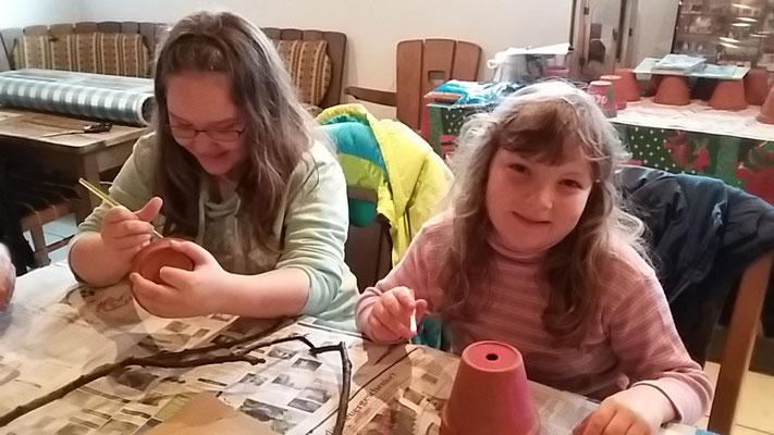 Joy und Rosalie bemalen ihren Tontopf.