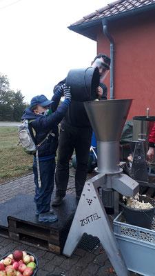 Die Kinder dürfen helfen die Äpfel in die Maschine zu kippen.