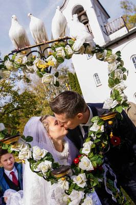 Brautpaar hinter dem Rosenherz mit weißen Tauben