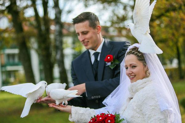 Brautpaar mit zahmen Tauben auf der Hand