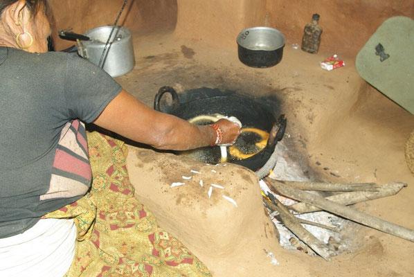 Mei, Mandhojs Frau, drückt aus der Hand schöne Teigkringel ins heiße Fett.