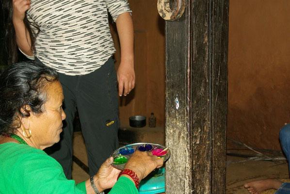 Mandhojs Schwester bringt ein Tika an einem Pfosten an.