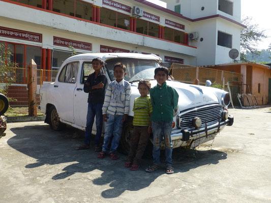 Jungs posieren vor einem Schrottauto