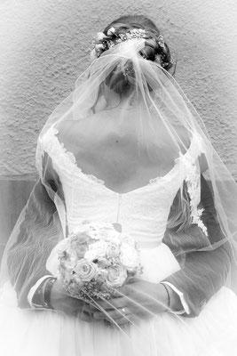 Braut sitzt auf Bräutigam