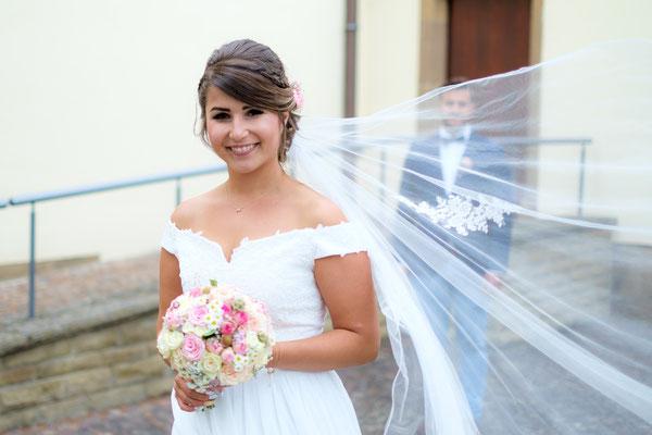 Brautschleier im Wind mit Bräutigam