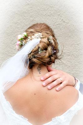 Braut von hinten mit Hand vom Bräutigam am Hals