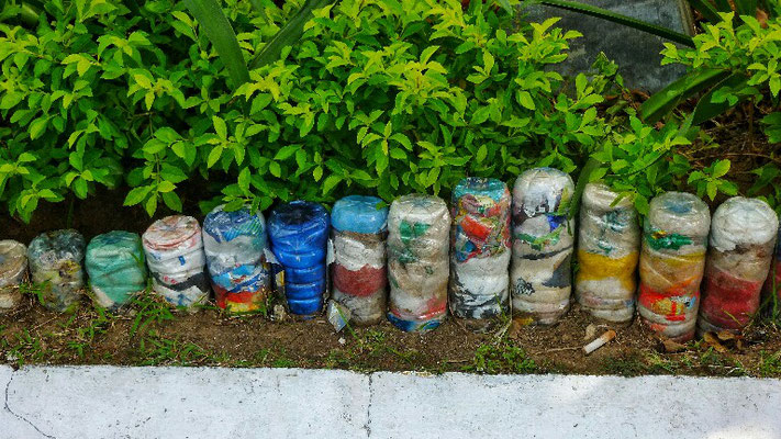 Müll in Plastikflaschen als Strassenrand Deko