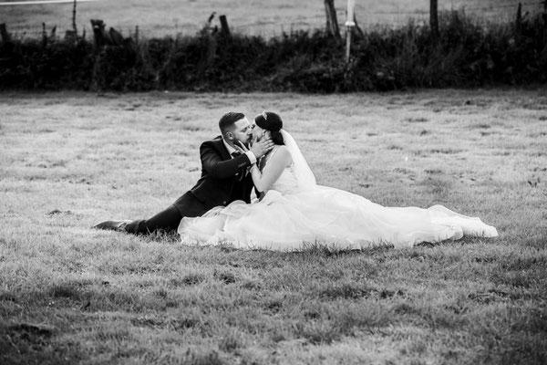 Brautpaar sitzt auf Wiese