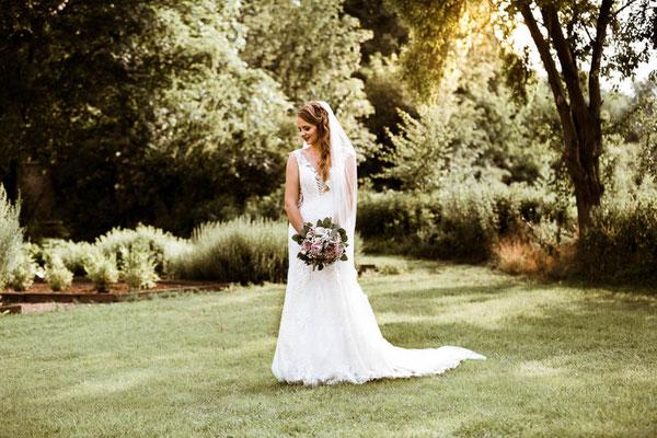 Braut steht mit Brautstrauß