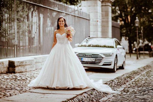 Braut steht vor Hochzeitsauto in Braunschweig
