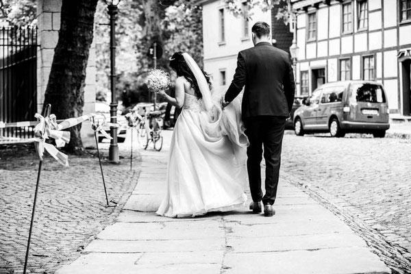 Brautpaar gehen zum Hochzeitsauto in Braunschweig