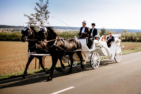 Hochzeitskutsche mit Brautpaar