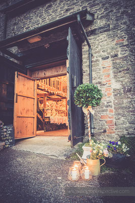 69-westcott-barton-wedding-photography-north-devon-barn-entrance-nighttime-candles