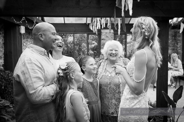 61-westcott-barton-wedding-photography-north-devon-bride-guests-chat-smile
