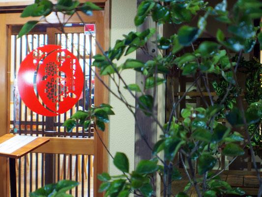 植栽と店舗入口の家紋