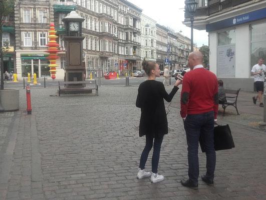 """""""Co ludzie sądzą o…"""" – jedna z rozmów prowadzonych przez Monikę podczas sondy ulicznej  (w tle żółto- czerwona współczesna rzeźba, na której temat zbierano opinie) – fot. Janusz Białas"""