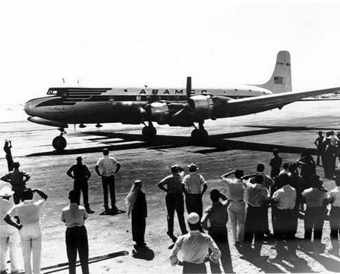 Group of people looking to the airplane The Flying Camel after landing in Dhahran 1950's