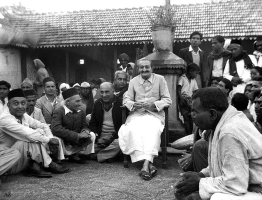 7th Nov.  Meher Baba at the Harijan dharamshala.  Baba's men Mandali are on the left, Bhagirath Tiwari (standing in jacket), Dattu Mehendarge, Sadashiv Patil( black cap & scarf), Eruch J.Photo taken by Panday.