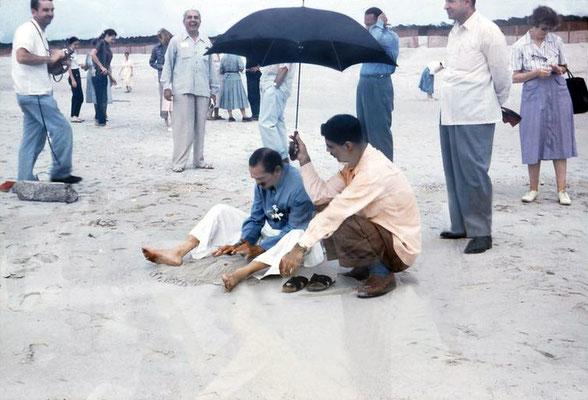 Meher Baba on Center Beach ( Arcadia Beach ) at Myrtle Beach, Sc. Eruch Jessawala holding the umbrella and Lud Dimpfl looking on. Meherjee Karkaria standing behind. Don Stevens on the far left.  Image captured by Anthony Zois from a film by Sufism Reorien