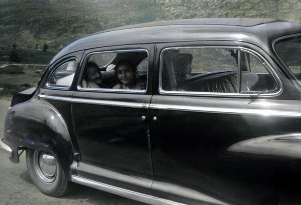 6th Aug. 1952. Baba with Mehera next to him & Mani on far side of their car, on their way to Locarno from Zurich. Image colourized by Anthony Zois.