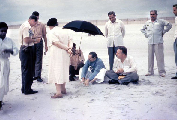 Meher Baba on Center Beach ( Arcadia Beach ) at Myrtle Beach, Sc. Eruch Jessawala holding the umbrella and Lud Dimpfl looking on. Meherjee Karkaria, Adi K Irani & Don Stevens standing behind. Elizabeth Patterson,Darwin Shaw & Beryl Williams on  far left.