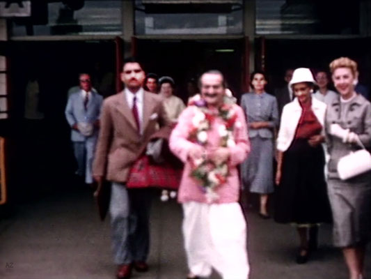 Idlewild Airport : Meher Baba outside the airport with Eruch Jessawala & Marion Florsheim ( R ). Ella Winterfeldt ( behind ) look on. Image captured by Anthony Zois from a film by Sufism Reoriented.