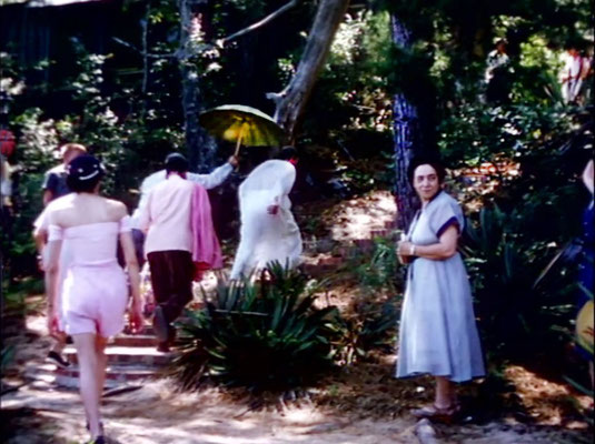 1956 ; Meher Center, Myrtle Beach, SC. ; Meher Baba walking up the steps from the bridge. Annarosa in pink summer outfit & her mother Theresa DiBlasio on the right. The images were captured by Anthony Zois from a film by Sufism Reoriented
