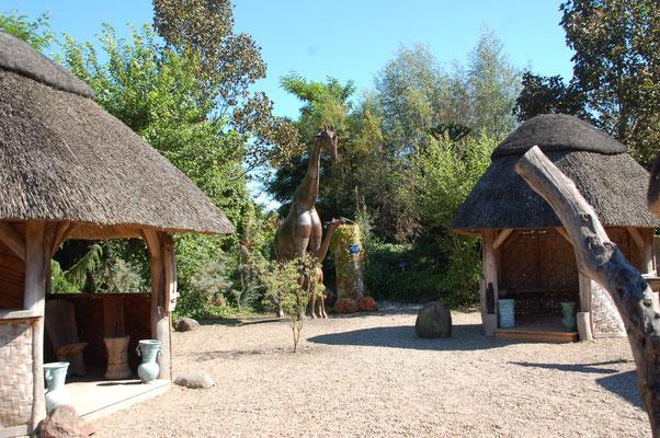 Afrikanischer Garten mit lebensgroßen Giraffen und Nachbauten von namibischen Himba-Hütten