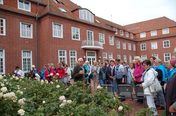 Antonius Bösterling (mitte) informiert vor der Katholischen Akademie Stapelfeld über die Landschaftsarchitektur der Einrichtung