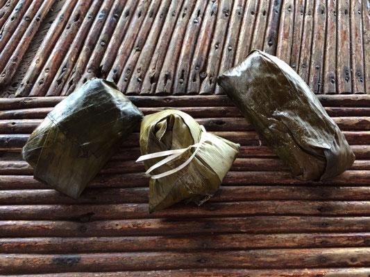 In Bananenblätter eingewickelter Sticky Rice mit Banane, Kokos oder Bohnen